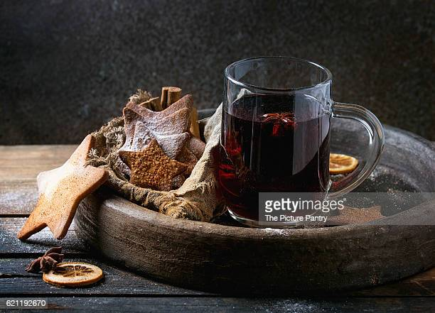 Glass mug of hot red mulled wine spices, sugar shortbread cookies star shape, anise and cinnamon powder