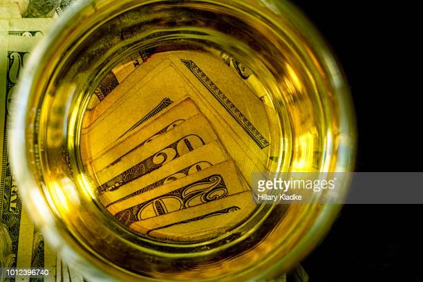 Glass of alcohol over money