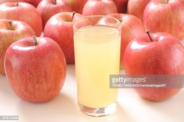 Glass of apple juice amongst apples