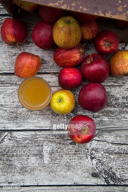 Glass of apple juice and red apples on wood