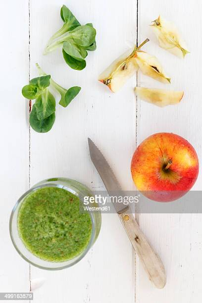 Glass of apple lamb's lettuce smoothie, apple, kitchen knife and lamb's lettuce on white wooden table
