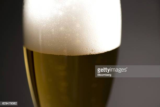 A glass of Asahi Breweries Ltd's Asahi Super Dry beer sits displayed for a photograph in Tokyo Japan on Tuesday Dec 13 2016 Asahi agreed to buy...