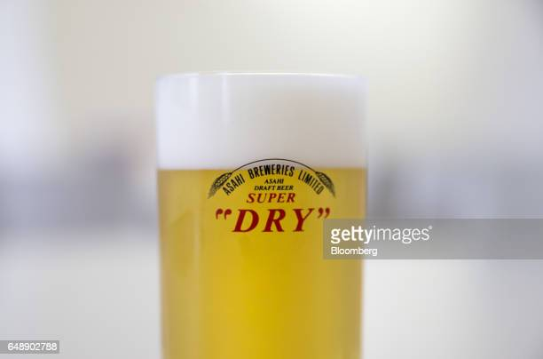 A glass of Asahi Super Dry beer sits on the table at the Asahi Kanagawa Brewery operated by Asahi Breweries Ltd a unit of Asahi Group Holdings Ltd in...