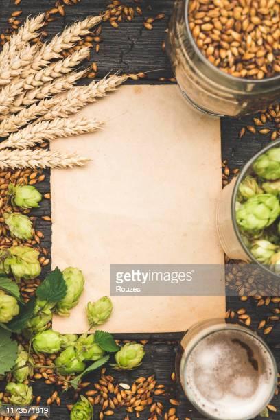 空の紙シートでテーブルの上にビールと食材のガラス - ラガービール ストックフォトと画像