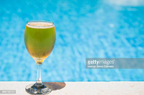 A glass of beer at the edge of the pool