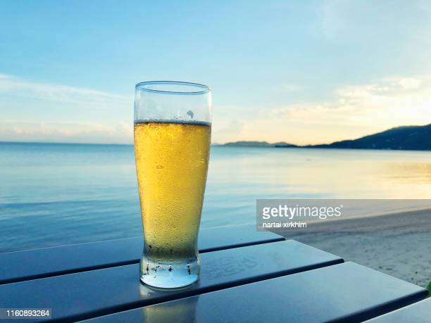 glass of beer on table at seaside - ビアグラス ストックフォトと画像