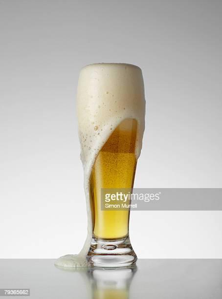 Glass of beer overflowing indoors