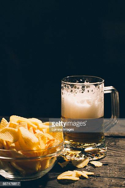 Glass of beer with bowl of potato chips