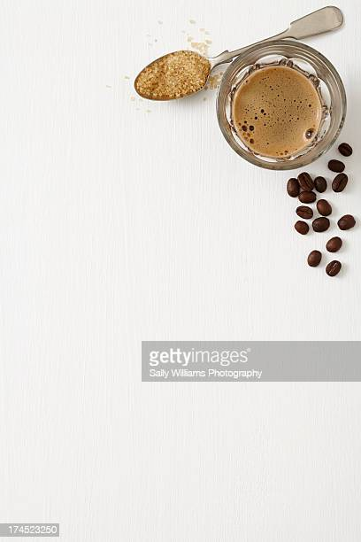 A glass of black coffee with beans and spoon