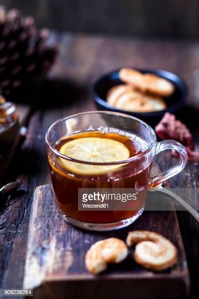 Glass of black tea with slice of lemon and rock sugar on wooden table