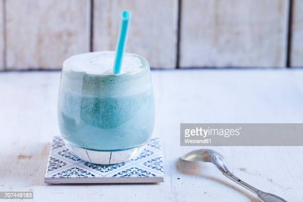 Glass of blue coloured latte with spirulina algae, vegan plant milk, ginger and rice syrup