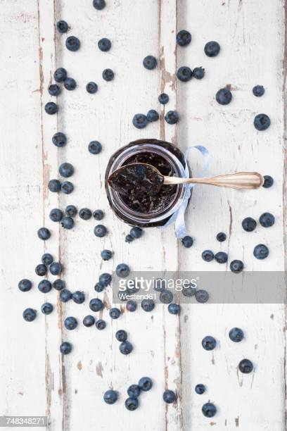 Glass of blueberry jam and blueberries on white wood