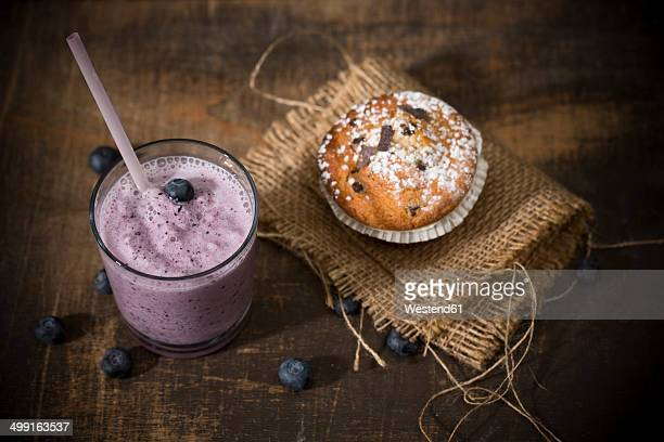 Glass of blueberry milkshake, blueberry muffin and blueberries on wooden table, elevated view