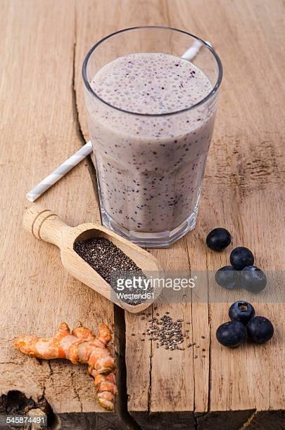 Glass of blueberry smoothie, wooden shovel of chia seeds, curcuma and blueberries on wood