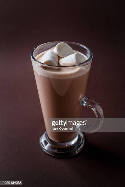 Glass of cacao with three marshmallows on elegant dark brown background