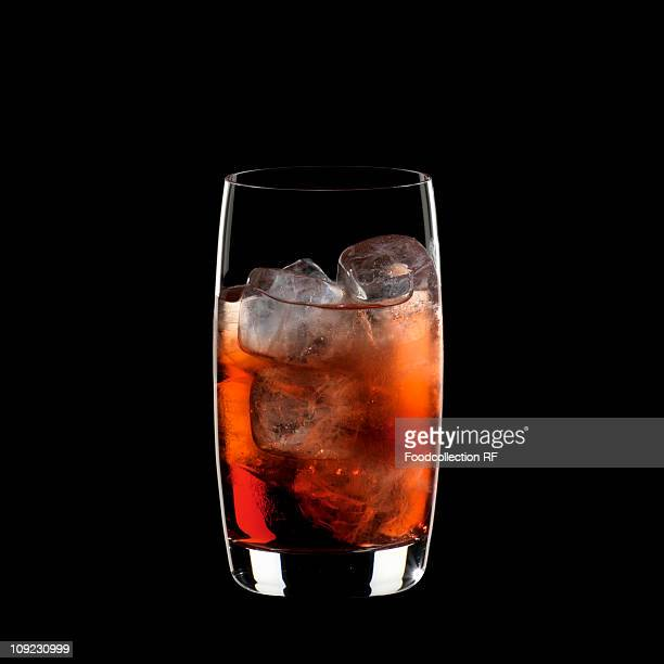 Glass of campari soda with ice cubes against black background, close-up