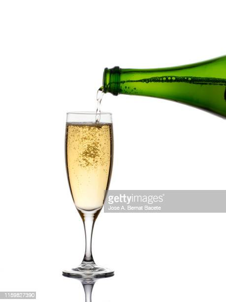 a glass of champagne and bottle on a white background. - champagne coloured stock photos and pictures