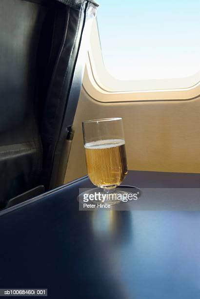 Glass of champagne on table in airplane