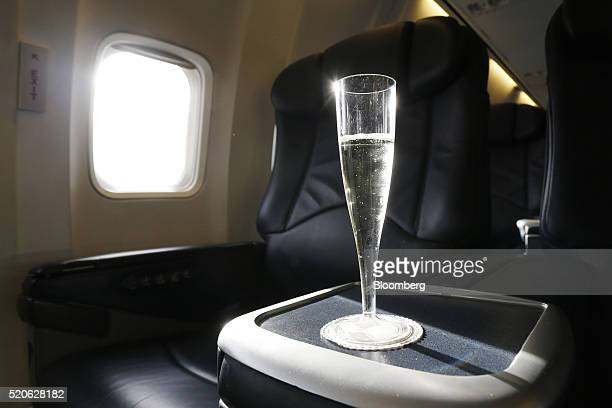A glass of champagne sits on a tray table in the cabin of the Ryanair Holdings Plc corporate jet before a flight to Dublin Ireland on Tuesday April...
