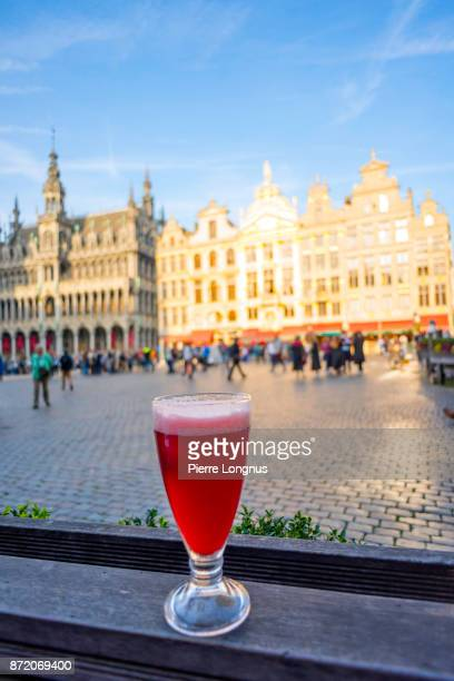 Glass of Cherry flavored traditional belgian beer on an outdoor counter on The Grand Place, UNESCO World Heritage Site, Brussels, Belgium