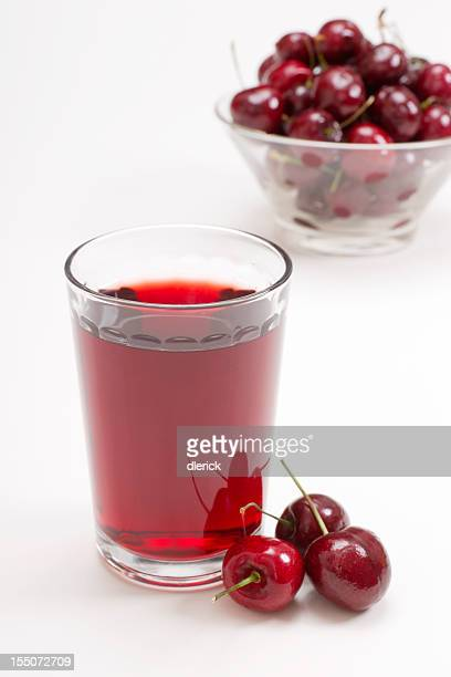 glass of cherry juice with cherries in background