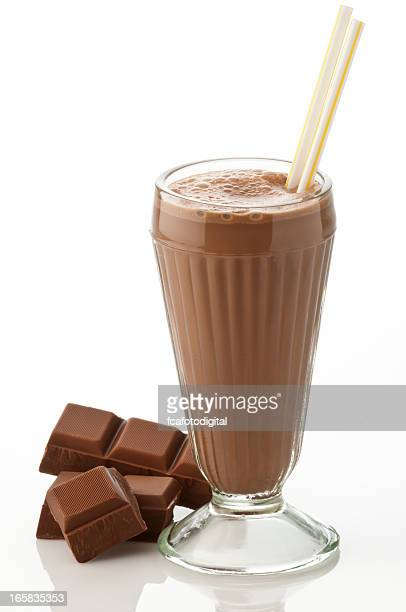 Glass of chocolate milkshake with chocolate chunks on white