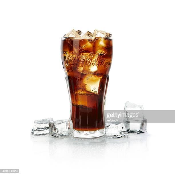 ガラスのコーラに氷を入れます。 - コークス ストックフォトと画像