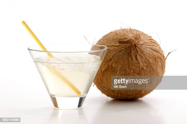 glass of coconut water with ice, a straw, and a whole coconut next to it on a white background - coconut water stock pictures, royalty-free photos & images