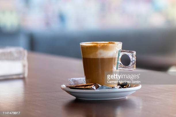 glass of coffee with beautiful latte art on the wooden table. - latte stock pictures, royalty-free photos & images