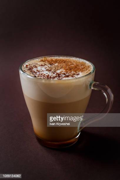 Glass of coffee with chocolate topping on elegant dark brown background