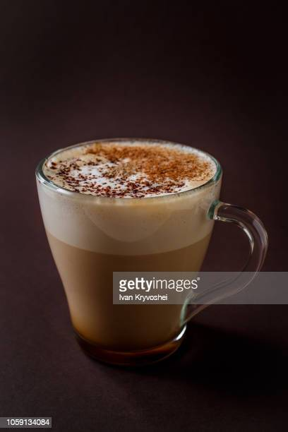 glass of coffee with chocolate topping on elegant dark brown background - cappuccino - fotografias e filmes do acervo