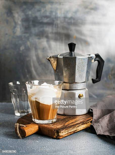 Glass of coffee with ice cream and steel moka pot on on rustic wooden board.