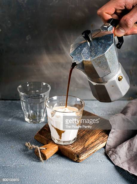 Glass of coffee with ice cream on rustic wooden board. Drink is poured from steel Italian Moka pot held by man's hand