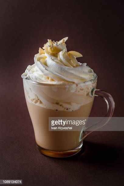 Glass of coffee with whipped cream and almonds shaving on elegant dark brown background