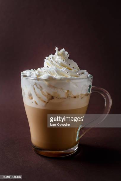Glass of coffee with whipped cream on elegant dark brown background