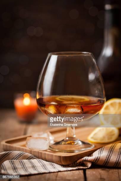 Glass of cognac on dark background