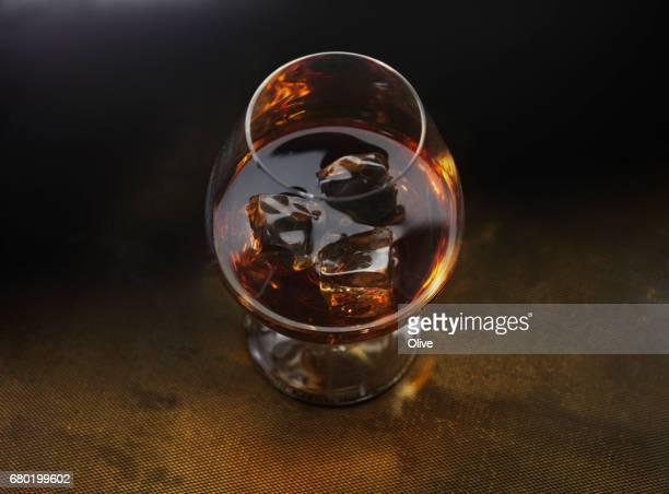 glass of cognac on dark gold background