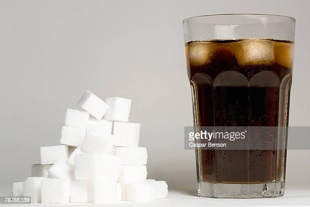 a glass of coke and a heap of sugar cubes - sugar pile stock pictures, royalty-free photos & images