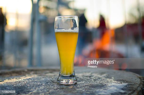 A glass of cold beer on a frozen log table