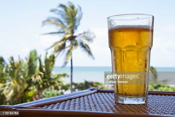 A glass of cold beer on a table with a view of a beach
