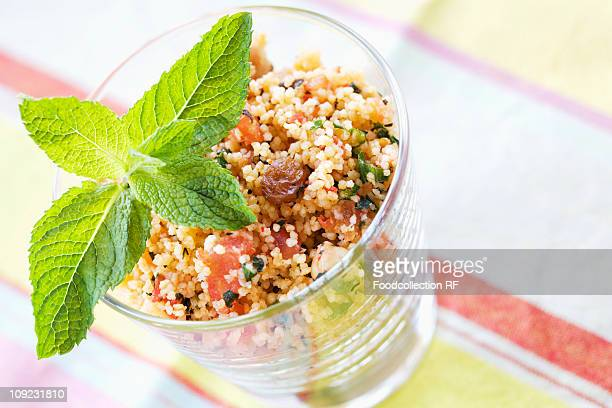 glass of couscous tabbouleh with vegetables, raisins and mint, close-up - bulgur wheat stock pictures, royalty-free photos & images