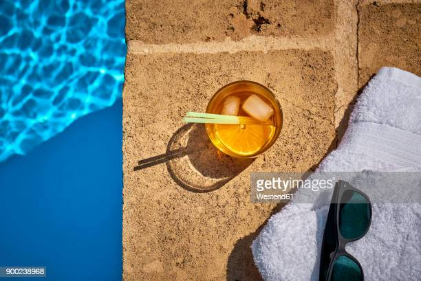 glass of crodino, sunglasses and towel at the poolside - poolside stock pictures, royalty-free photos & images