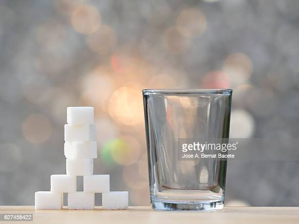 Glass of crystal and heap of sugar cubes , it is the equivalent in sugar to a drink of refreshment sweetened