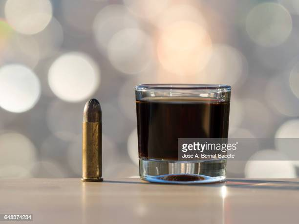 Glass of crystal of chupito fill of an alcoholic drink and a bullet of pistol, , illuminated by the light of the Sun