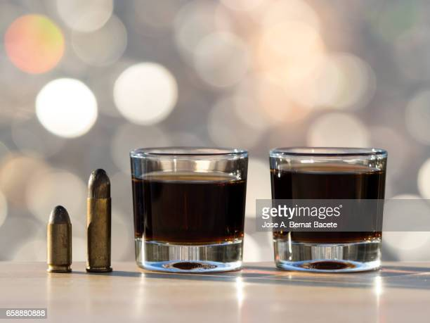 glass of crystal of chupito fill of an alcoholic drink and a bullet of pistol, , illuminated by the light of the sun - dos objetos stock pictures, royalty-free photos & images