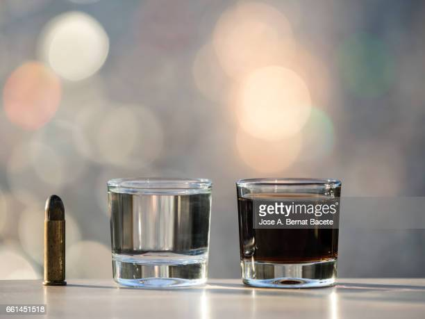 glass of crystal of chupito fill of an alcoholic drink and a bullet of pistol, , illuminated by the light of the sun - bebida stock pictures, royalty-free photos & images