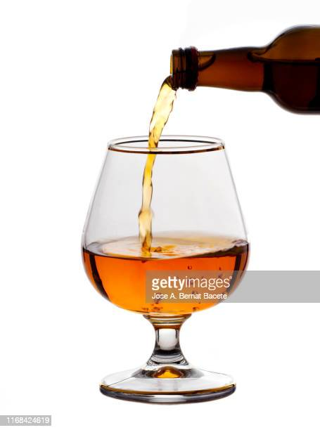 glass of crystal of chupito fill of an alcoholic drink, filling them with a bottle of drink, (shot of spirit). - liqueur stock pictures, royalty-free photos & images