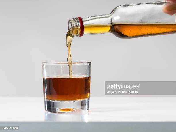 glass of crystal of chupito fill of an alcoholic drink, filling them with a bottle of drink. - cirrhosis stock pictures, royalty-free photos & images
