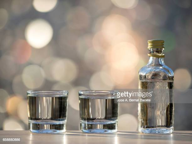 glass of crystal of chupito fill of an alcoholic liqueur  drink, illuminated by the light of the sun - bebida stock pictures, royalty-free photos & images
