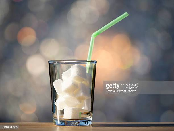 glass of crystal with a straw  and heap of sugar cubes , it is the equivalent in sugar to a drink of refreshment sweetened - bebida fría fotografías e imágenes de stock